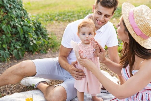 Uśmiechnięta młoda rodzina z małą córeczką spędzającą razem czas