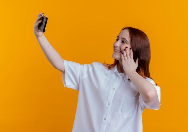 Uśmiechnięta młoda ruda dziewczyna bierze selfie i kładzie rękę na policzku na żółto