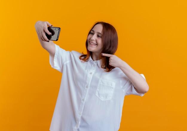 Uśmiechnięta młoda ruda dziewczyna bierze selfie i wskazuje na telefon na białym tle na żółtej ścianie