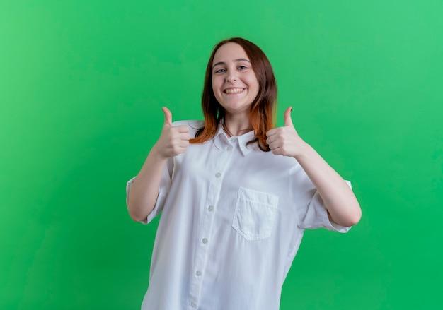 Uśmiechnięta młoda ruda dziewczyna jej kciuki do góry na białym tle na zielono