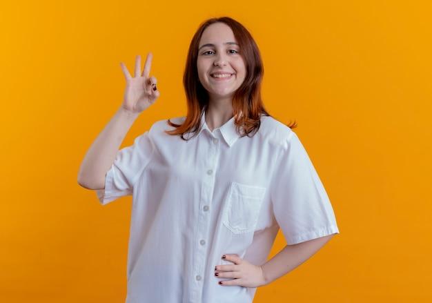 Uśmiechnięta młoda ruda dziewczyna pokazuje okey gest i kładzie rękę na biodrze na białym tle na żółtym tle