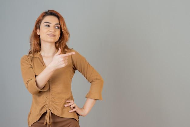 Uśmiechnięta młoda ruda trzymająca palec w górze i odwracająca wzrok na szarej ścianie