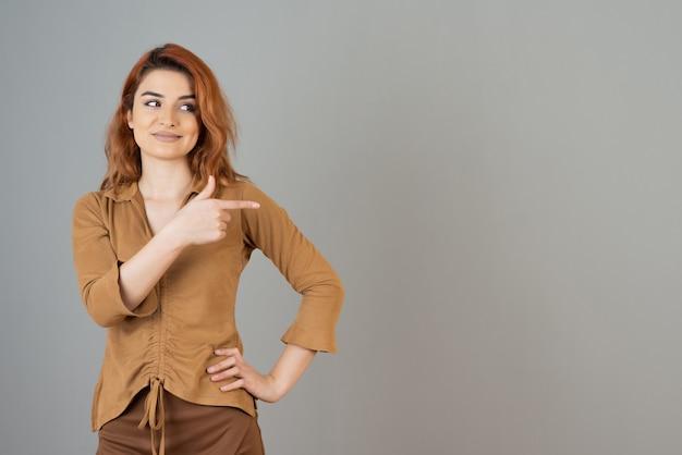 Uśmiechnięta młoda ruda wskazująca palcem w bok i odwracająca wzrok na szarej ścianie