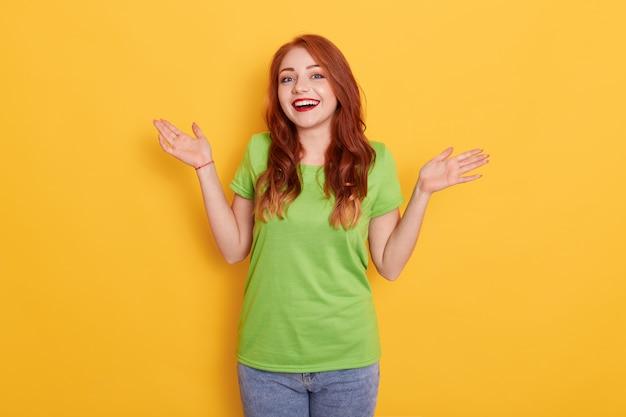 Uśmiechnięta młoda rudowłosa dziewczyna kobieta w ubranie, pozowanie na białym tle, rozkładając ręce na bok
