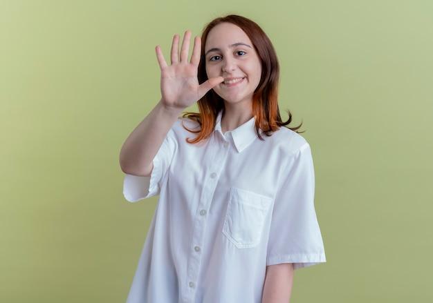 Uśmiechnięta młoda rudowłosa dziewczyna pokazując pięć na białym tle na oliwkowej ścianie