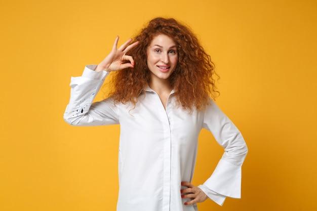 Uśmiechnięta młoda rudowłosa dziewczyna w białej koszuli pozuje na białym tle na żółtopomarańczowej ścianie