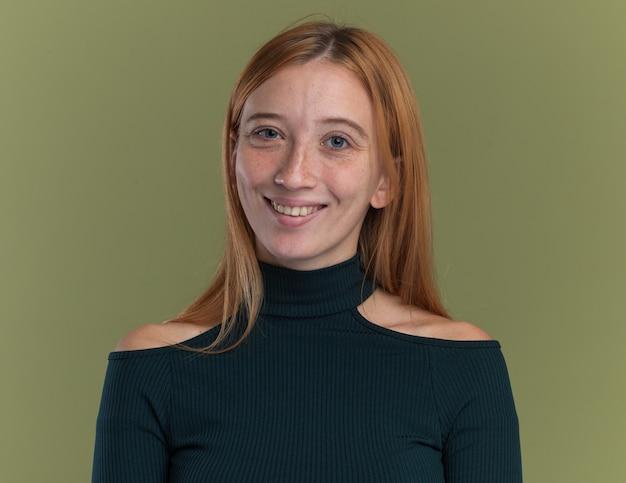 Uśmiechnięta młoda rudowłosa imbirowa dziewczyna z piegami odizolowana na oliwkowozielonej ścianie z miejscem na kopię
