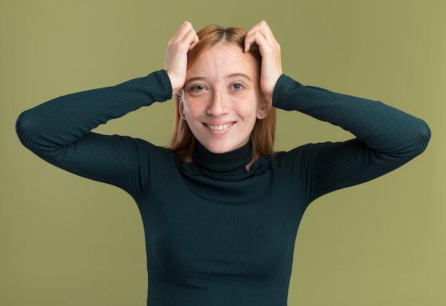 Uśmiechnięta młoda rudowłosa ruda dziewczyna z piegami kładzie ręce na głowie i patrzy na kamerę