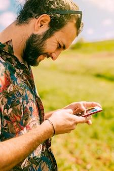 Uśmiechnięta młoda samiec używa telefon komórkowego w wiejskim