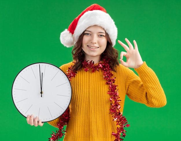 Uśmiechnięta młoda słowiańska dziewczyna z czapką mikołaja i girlandą na szyi trzyma zegar i gestykuluje znak ok odizolowany na zielonym tle z miejscem na kopię