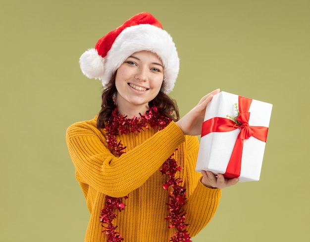 Uśmiechnięta młoda słowiańska dziewczyna z santa hat i girlandą wokół szyi trzyma świąteczne pudełko na białym tle na oliwkowozielonej ścianie z kopią przestrzeni