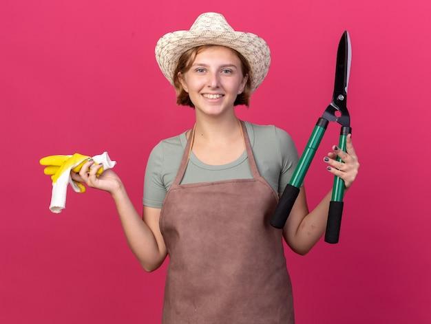 Uśmiechnięta młoda słowiańska ogrodniczka w kapeluszu ogrodniczym, trzymająca nożyczki ogrodnicze i rękawiczki odizolowane na różowej ścianie z miejscem na kopię