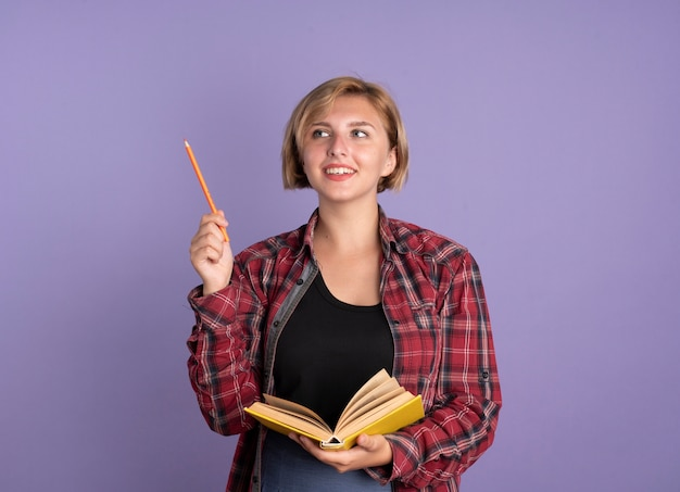 Uśmiechnięta młoda słowiańska studentka trzyma ołówek i książkę patrząc na bok