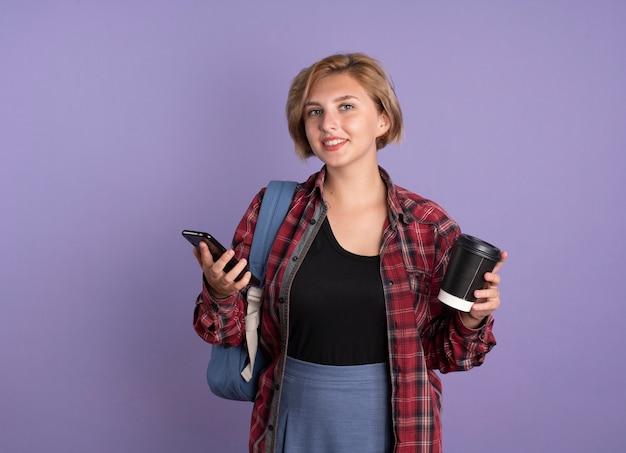 Uśmiechnięta młoda słowiańska studentka w plecaku trzyma papierowy kubek i telefon