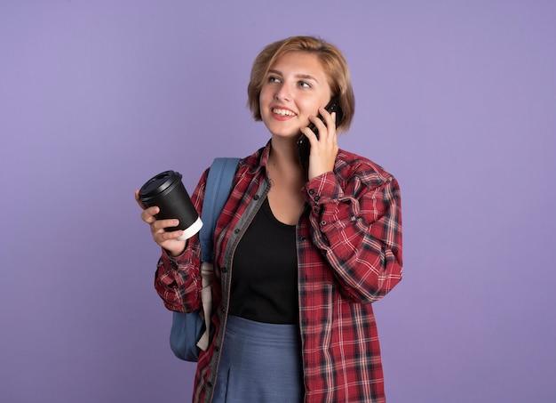 Uśmiechnięta młoda słowiańska studentka w plecaku trzyma papierowy kubek rozmawia przez telefon, patrząc na bok