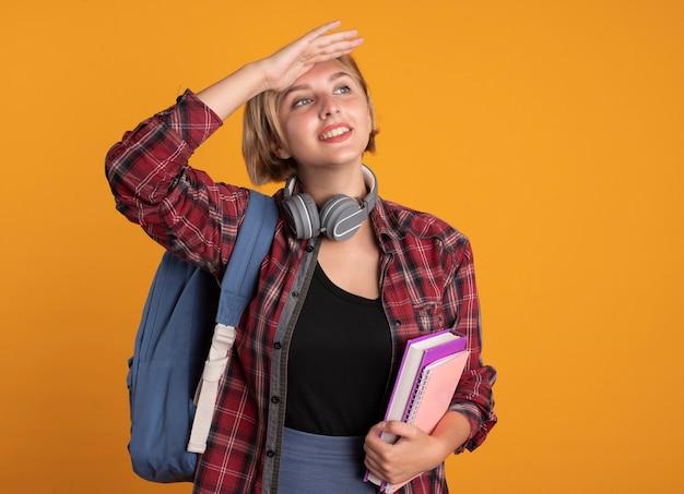 Uśmiechnięta młoda słowiańska studentka ze słuchawkami w plecaku trzyma dłoń na czole trzyma książkę i notatnik
