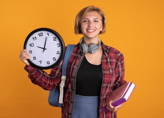 Uśmiechnięta młoda słowiańska studentka ze słuchawkami w plecaku trzyma książkę z zegarem i notatnik