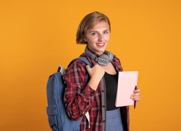 Uśmiechnięta młoda słowiańska studentka ze słuchawkami w plecaku trzyma notatnik i długopis, patrząc na kamerę