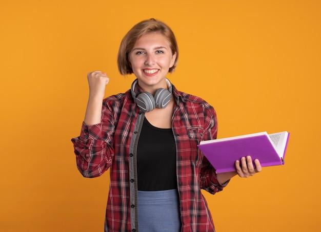 Uśmiechnięta młoda słowiańska studentka ze słuchawkami w plecaku trzyma pięść trzyma książkę