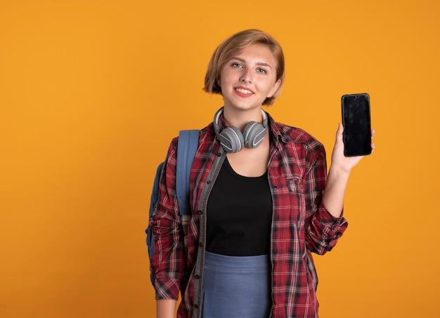 Uśmiechnięta młoda słowiańska studentka ze słuchawkami w plecaku trzymająca telefon