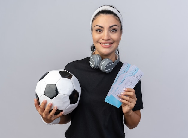 Uśmiechnięta młoda sportowa dziewczyna rasy kaukaskiej nosząca opaskę i opaski ze słuchawkami na szyi, trzymająca bilety lotnicze i piłkę nożną, patrząc na przód na białym tle na białej ścianie