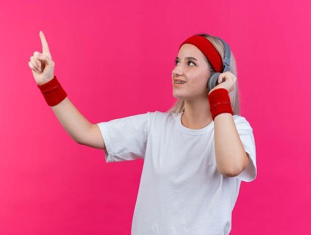 Uśmiechnięta młoda sportowa kobieta z szelkami na słuchawkach nosząca pałąk i opaski na rękę wygląda i wskazuje na bok na białym tle na różowej ścianie