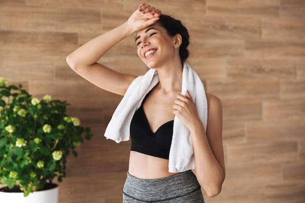 Uśmiechnięta młoda sportsgirl pozycja z ręcznikiem