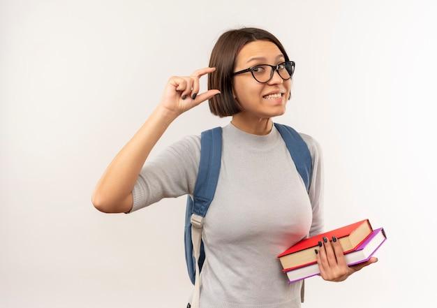 Uśmiechnięta młoda studencka dziewczyna w okularach iz powrotem trzymając książki pokazujące rozmiar na białej ścianie