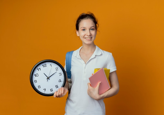 Uśmiechnięta młoda studentka całkiem żeński noszenie plecaka trzymając notes i zegar na białym tle na pomarańczowym tle z miejsca na kopię