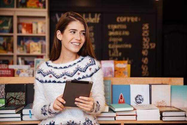 Uśmiechnięta młoda studentka korzystająca z komputera typu tablet w bibliotece