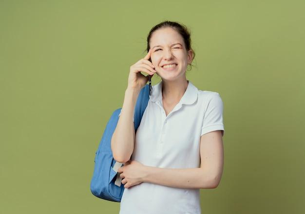 Uśmiechnięta młoda studentka ładna noszenie plecaka rozmawia przez telefon patrząc z boku ręką na nerce na białym tle na zielonym tle z miejsca na kopię