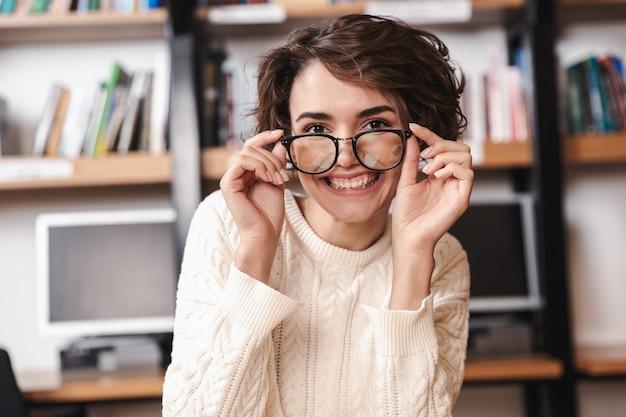 Uśmiechnięta młoda studentka studiuje siedząc przy biurku biblioteki, nosząc okulary