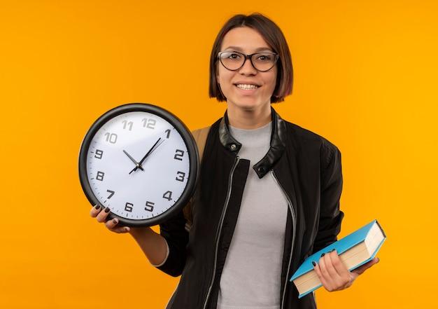 Uśmiechnięta młoda studentka w okularach i plecak trzymając książkę i zegar na białym tle na pomarańczowej ścianie