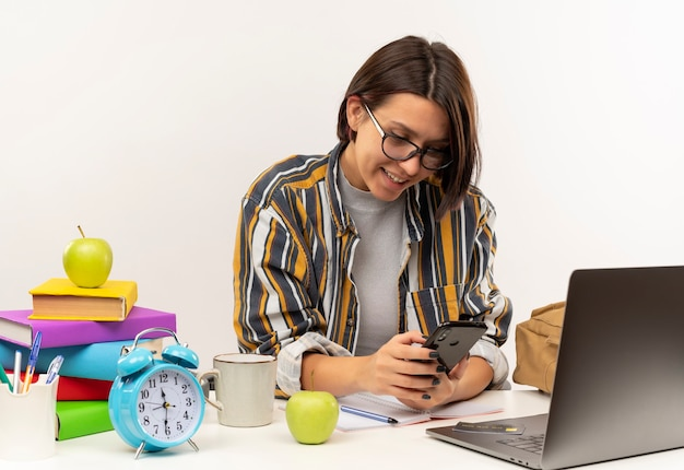 Uśmiechnięta młoda studentka w okularach siedzi przy biurku z narzędziami uniwersyteckimi przy użyciu telefonu komórkowego na białej ścianie