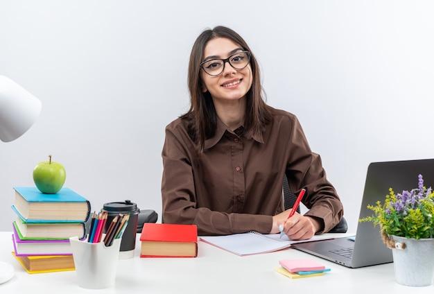 Uśmiechnięta młoda szkolna kobieta w okularach siedzi przy stole z szkolnymi narzędziami i pisze coś na zeszycie