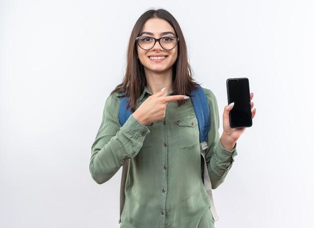 Uśmiechnięta młoda szkolna kobieta w okularach, trzymająca plecak i wskazująca na telefon