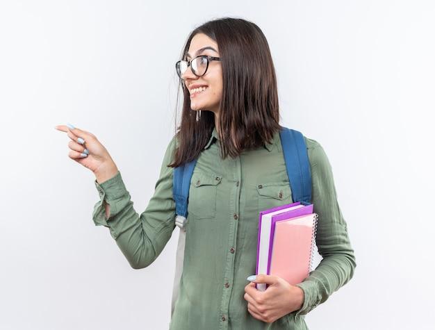 Uśmiechnięta młoda szkolna kobieta w okularach z plecakiem trzymająca książki wskazuje z boku