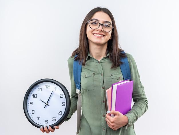 Uśmiechnięta młoda szkolna kobieta w okularach z plecakiem trzymająca książki z zegarem ściennym