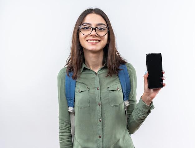 Uśmiechnięta młoda szkolna kobieta w okularach z plecakiem trzymającym telefon