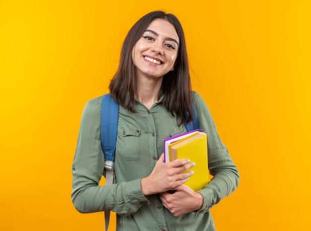 Uśmiechnięta młoda szkolna kobieta w plecaku trzymająca książki