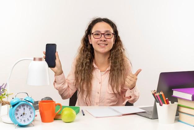 Uśmiechnięta młoda uczennica całkiem w okularach siedzi przy biurku z narzędziami szkolnymi, odrabiania lekcji, pokazując telefon komórkowy i kciuk do góry na białym tle na białej ścianie
