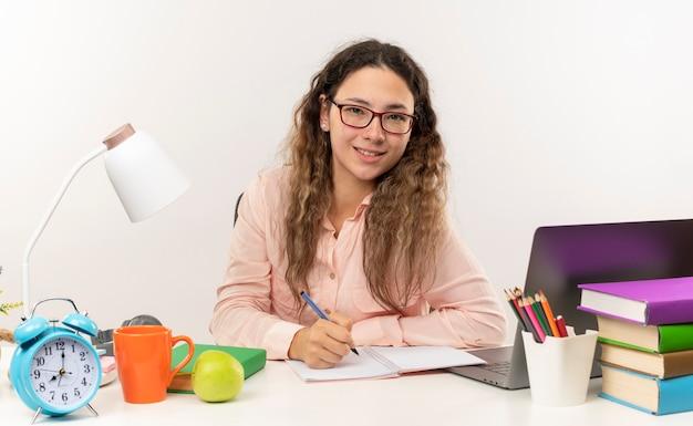 Uśmiechnięta młoda uczennica całkiem w okularach siedzi przy biurku z narzędziami szkolnymi, robi jej pracę domową, pisząc w notatniku na białej ścianie