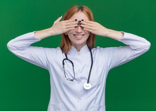 Uśmiechnięta młoda żeńska lekarka imbirowa nosząca medyczną szatę i stetoskop zakrywający oczy rękami odizolowanymi na zielonej ścianie