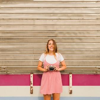 Uśmiechnięta młodej kobiety pozycja przed panwiową żelazną mienie kamerą w ręce