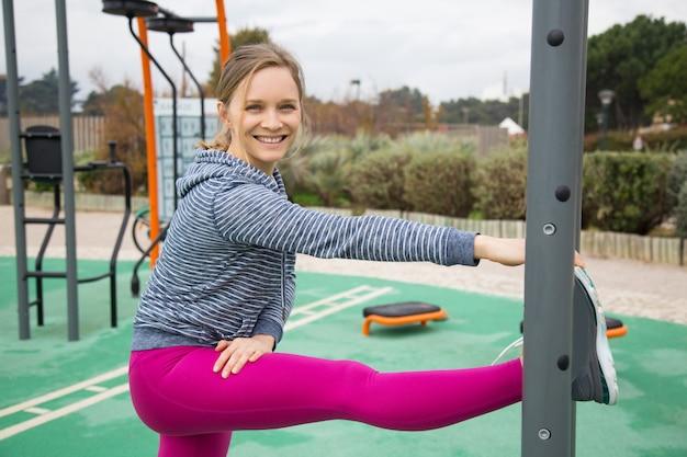 Uśmiechnięta młodej kobiety rozciągania noga na sportach gruntuje