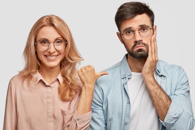 Uśmiechnięta modelka blondynka wskazuje kciukiem na niezadowolonego brata, który czuje się zdziwiony