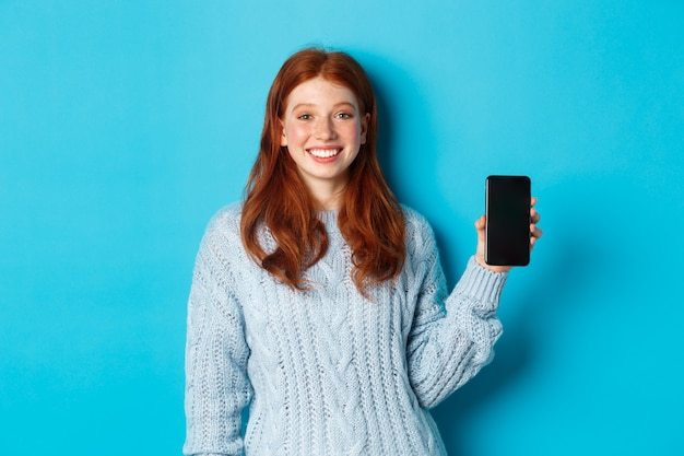 Uśmiechnięta modelka z rudymi włosami pokazująca ekran smartfona, trzymająca telefon i demonstrująca aplikację, stojąca na niebieskim tle