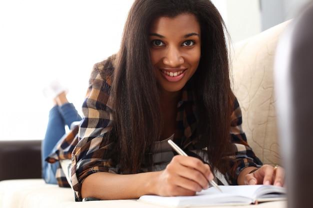Uśmiechnięta murzynka pisze opowieści w notatniku