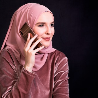 Uśmiechnięta muzułmańska kobieta opowiada na telefonie komórkowym w czarnym tle