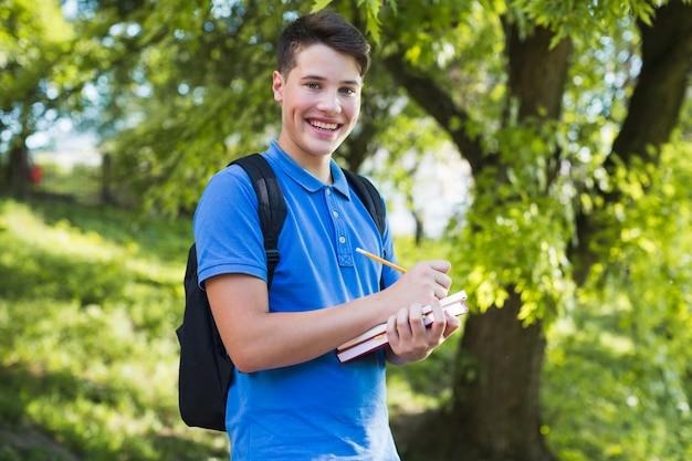 Uśmiechnięta nastolatek chłopiec dokonywania notatek